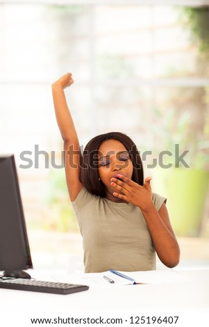 young african american woman yawning in front of desk - stock photo