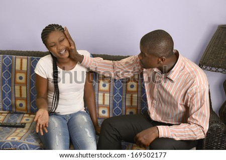 Young african beats his girlfriend, Studio Shot - stock photo