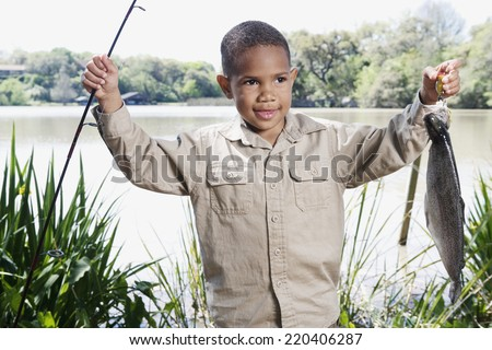Young African boy with fishing pole and fish - stock photo