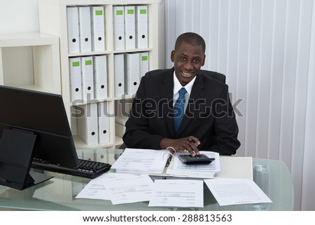 Young African Businessman Calculating Bills In Office - stock photo