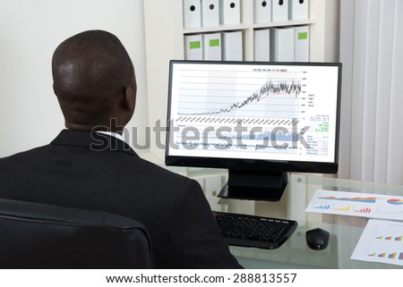 Young African Businessman Looking At Graph On Computer At Desk In Office - stock photo