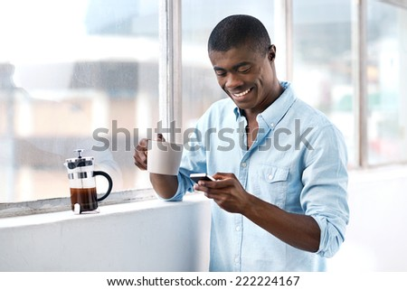 young african businessman with coffee and mobile phone at window in morning - stock photo