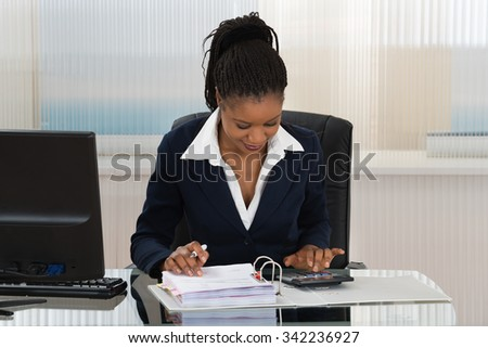 Young African Businesswoman Calculating Bills At Office Desk - stock photo