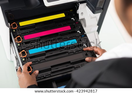 Young African Businesswoman Fixing Cartridge Near Photocopy Machine In Office - stock photo