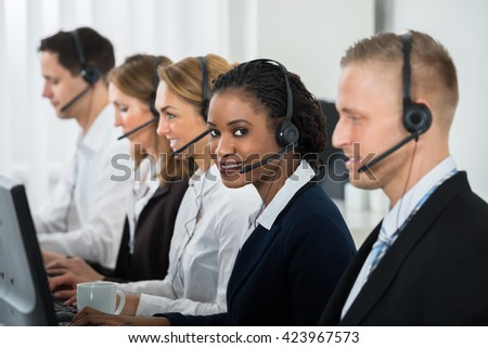 Young African Businesswoman With Headset Working With Other Colleagues In Call Center - stock photo