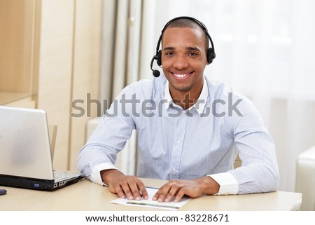 young african call center consultant with headset in office - stock photo