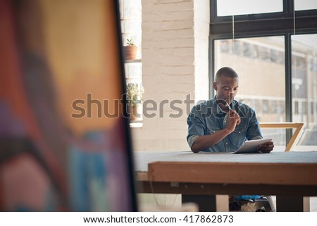 Young African entrepreneur thinking while writing down future plans - stock photo