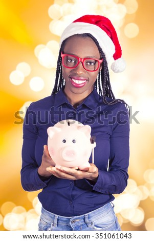 Young African girl with Christmas hat and a piggy bank  - stock photo