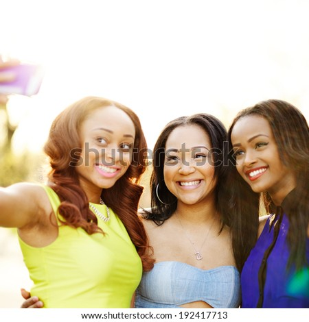 young african girls taking selfies with smart phone - stock photo