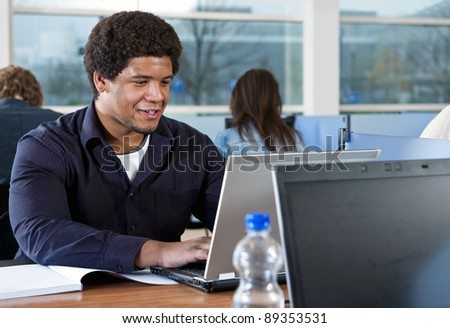 Young African man, studying in a library behind a laptop and his college notes with more people in the background - stock photo