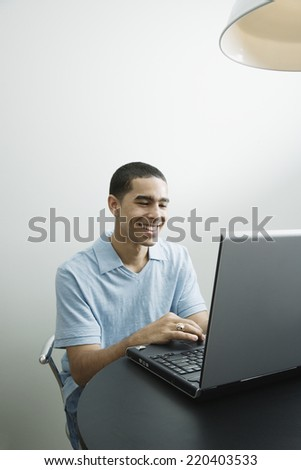 Young African man using laptop - stock photo