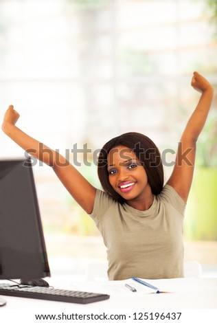 young african university student stretching before computer - stock photo