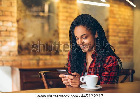 Young african woman at cafe drinking coffee and using mobile phone  - stock photo