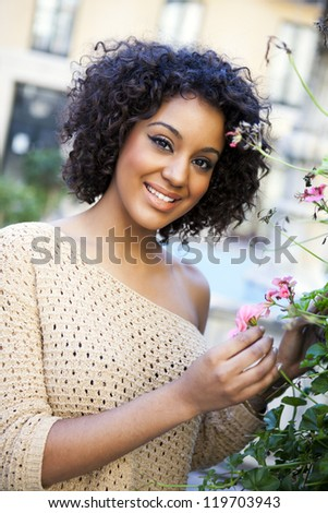 Young african woman in a park holding plants - stock photo