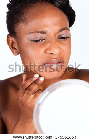 Young African woman in Studio doing body care and checking her face for pimples and spots with mirror for young and beautiful skin - stock photo