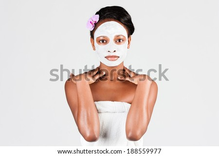 Young African woman in Studio doing body care with refreshing facial mask for young and beautiful skin and relaxation - stock photo