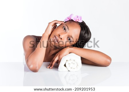 Young African woman in Studio doing body care with towel taking bath for young and beautiful skin and relaxation - stock photo