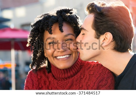 Young african woman is smiling while her boyfriend kissing her on the cheek. Close up face of young man kissing in woman's cheek while sitting at sidewalk cafe. Loving multi ethnic couple outdoor. - stock photo