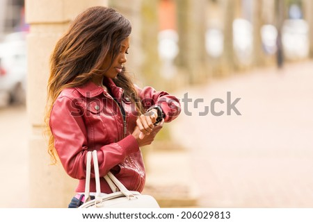 young african woman looking at her watch in urban street - stock photo