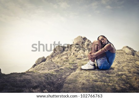 Young african woman sitting on a rock - stock photo