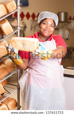 young african woman wearing heat-protected gloves preparing fresh bread loaves to be cooled on the rack - stock photo