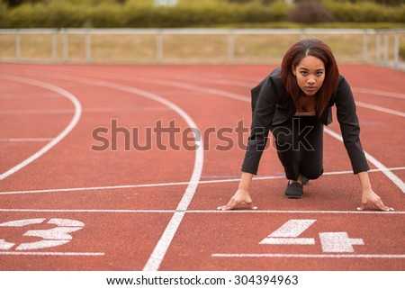 Young Afro-American Businesswoman Looking at the Camera While in a Start Position on Race Track. - stock photo