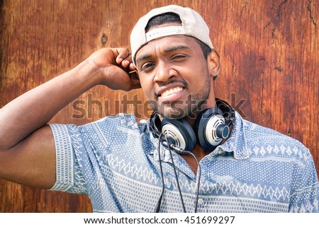 Young afro american man smiling at camera - Self confident black guy with cap staring into the eyes on wood background - Portrait of attractive african male wearing headphones - stock photo