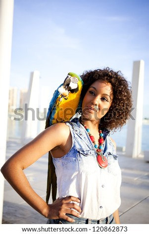 Young afro american woman with a blue macaw on her shoulder in the city - stock photo