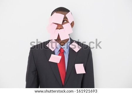 Young Afro businessman covered in blank notes over white background - stock photo