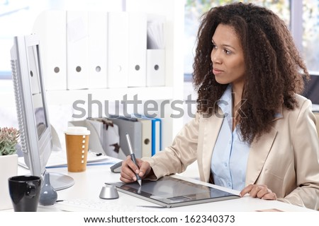 Young afro designer working at desk, using drawing pad. - stock photo