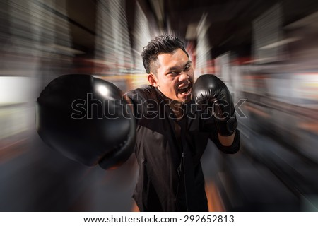 young aggressive businessman training shadow boxing at gym with gloves throwing vicious punch in angry rage face expression, fighting business concept, motion blur background. - stock photo