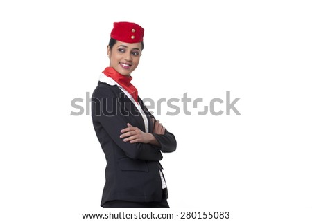 Young air hostess with arms crossed looking away against white background - stock photo