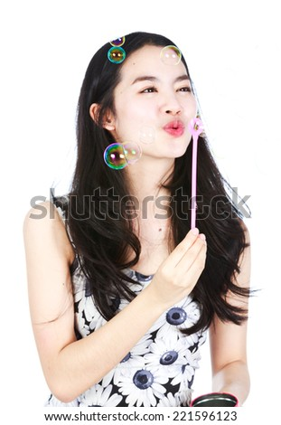 Young aisan lady blowering bubbles - stock photo