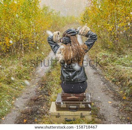 Young alone slim girl in a black leather jacket with fur collar sitting on the road in a forest in an old retro suitcase on snowy background of the autumn snowfall No face  - stock photo