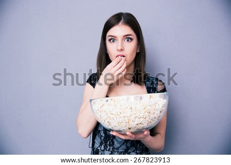 Young amazed woman eating popcorn over gray background. Looking at camera - stock photo