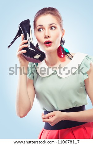 Young amazed woman using a shoe like a telephone holding it near her face and talking, blue background. Pin-up style. - stock photo