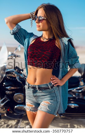 Young amazing sexy woman posing  near motorbike on the beach, wearing stylish crop top , shirts, have perfect fit slim tamed body and long hairs. Outdoor lifestyle  portrait.  - stock photo