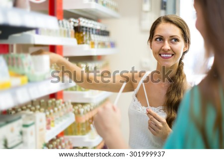 young american girl chooses perfume in the shop - stock photo