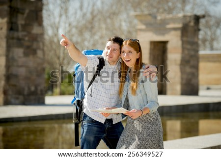 young American student and tourist couple visiting reading city map pointing monument carrying expedition backpack in holiday tourism and vacation travel concept - stock photo