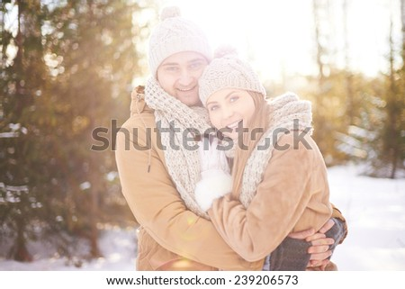 Young amorous couple embracing and looking at camera outdoors - stock photo