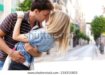 Young and attractive couple on holiday, kissing and embracing while sightseeing a destination city street, traveling outdoors. Love, passion and relationships. - stock photo