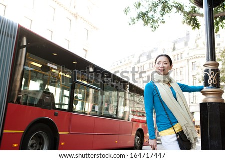 Young and attractive Japanese tourist woman enjoying sightseeing in the destination city of London with red buses and classic buildings around her, during a sunny day on holiday, outdoors. - stock photo