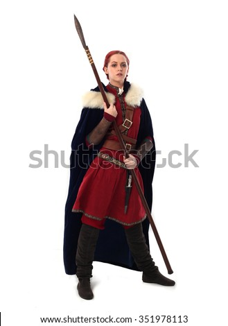 young and attractive red haired  female warrior,  wearing a red medieval tunic and leather Armour, velvet fur lined cloak. holding a spear as a weapon. isolated on a white background. - stock photo