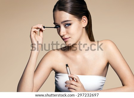 Young and attractive woman applying mascara / photos of appealing brunette girl on beige background - stock photo