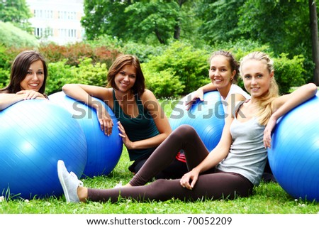 Young and attractive womans doing fitness exercises in park - stock photo