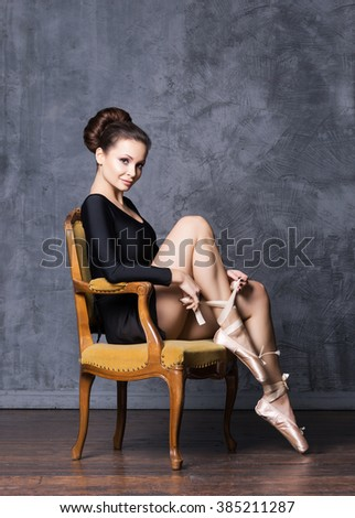 Young and beautiful ballerina with a perfect body sitting on a vintage armchair.  - stock photo