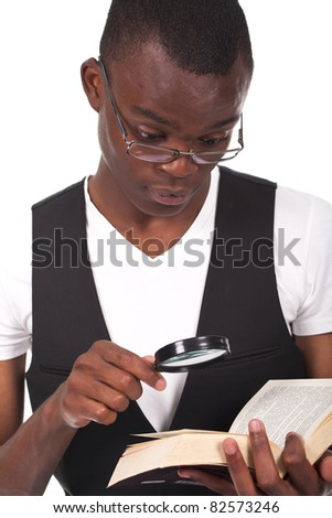 young and beautiful black man holding a magnifying glass and reading a book - stock photo
