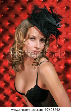 Young and beautiful blonde dancer wearing Black corset, stockings and designer's hat over vintage red background - stock photo