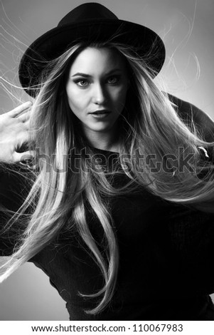 Young and beautiful blonde in black with hat on her had - stock photo