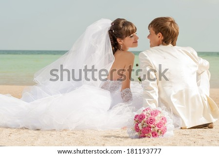 Young and beautiful bride and groom on the beach  - stock photo
